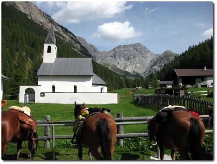 Kirche S-charl und Pferde bereit für den touristischen Ausritt